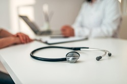 Healthcare and medicine concept. Medical stethoscope on desk. Doctor and patient in the background. Focus on the foreground, on the stethoscope.