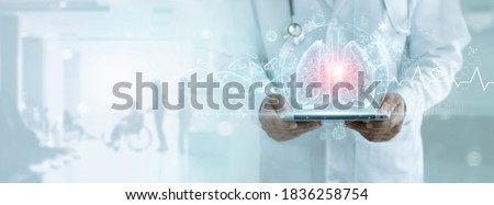 Healthcare and medicine, Covid-19, Doctor holding tablet and diagnose virtual Human Lungs with coronavirus spread inside on modern interface screen on hospital, Innovation and Medical technology. Foto stock ©
