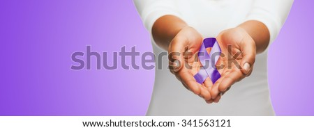 healthcare and social problems concept - close up of woman hands holding purple domestic violence awareness ribbon over violet background