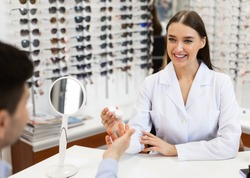 Healthcare And Vision Correction Concept. Happy female doctor optometrist giving plastic container with contacts lens to man customer sitting at desk. Consultation at the optics store