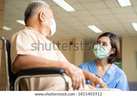 Healthcare concept, Asian nurse taking care and talking of mature male patient sitting on wheelchair in hospital. Woman and senior man wearing surgical face mask for protection of The COVID infection.