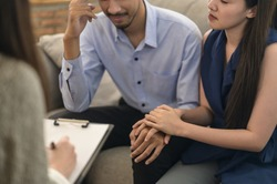Healthcare concept: Young Asian couple received a consultant with professional psychologist doctor in psychotherapy session or counsel diagnosis health. Wife encourage her husband during psychotherapy