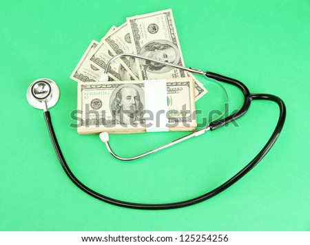 Healthcare cost concept: stethoscope and dollars on green  background