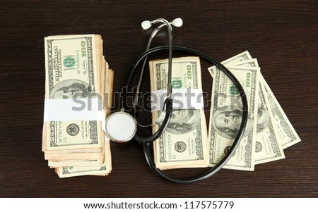 Healthcare cost concept: stethoscope and dollars on wooden background - stock photo