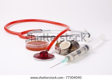 healthcare cost money coins and bills with a red stethoscope and blood sample