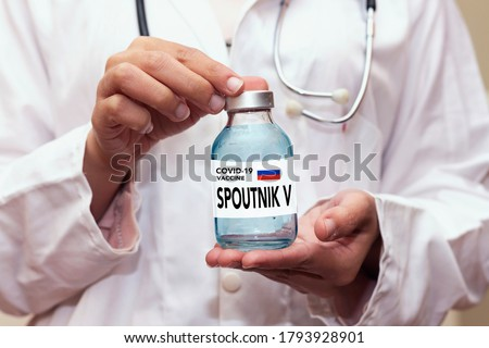 Healthcare cure concept with a hand in blue medical gloves holding Coronavirus, Covid 19 virus, Spoutnik V new russia vaccine vial