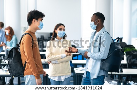 Healthcare, Education, Lifestyle And People Concept. Group of smiling diverse international students wearing protective medical masks and talking, standing in lecture hall at the university