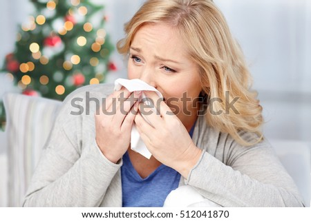 healthcare, flu, christmas, and people concept - ill woman blowing nose to paper napkin