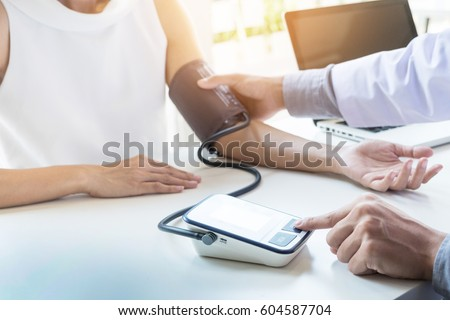 healthcare, hospital and medicine concept - doctor and patient measuring blood pressure. #604587704