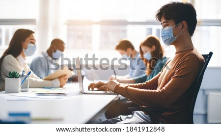 Healthcare, Lifestyle And People Concept. Group of diverse international students or employees wearing protective medical masks and using laptop computers, studying and working. New Normal