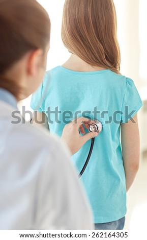 healthcare, medical exam, people, children and medicine concept - close up of girl and doctor with stethoscope listening to heartbeat