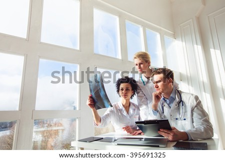 Healthcare, medical: Group of multi-ethnic doctors discuss and looking x-ray in a clinic or hospital