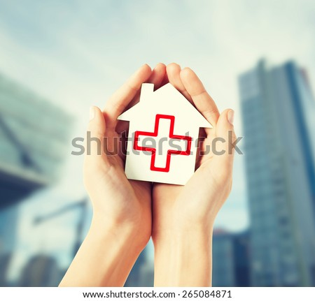 healthcare, medicine and charity concept - hands holding white paper house with red cross sign