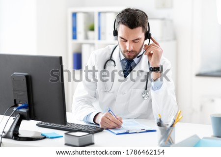healthcare, medicine and technology concept - male doctor with headset and clipboard working at hospital