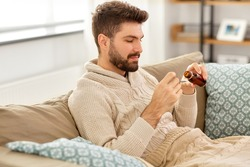 healthcare, people and medicine concept - sick man pouring antipyretic or cough syrup from bottle to spoon