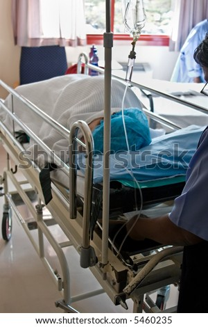 Healthcare personnel carry one patient after surgery in the recovery room