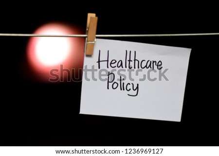 Healthcare Policy handwriting on paper. Hanged with a clothes clips, medical and education concept. light blur background #1236969127