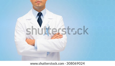 healthcare, profession, people and medicine concept - close up of male doctor in white coat with sky blue prostate cancer awareness ribbon