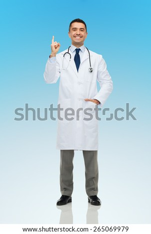 healthcare, profession, people and medicine concept - happy smiling male doctor in white coat pointing finger up over blue background