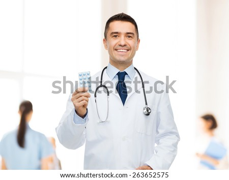 healthcare, profession, people and medicine concept - smiling male doctor in white coat with tablets over group of medics at hospital background