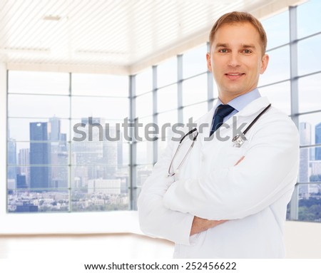 healthcare, profession, people and medicine concept - smiling male doctor with stethoscope in white coat over clinic background