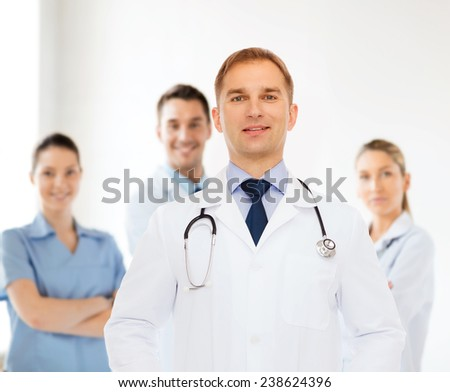 healthcare, profession, teamwork, people and medicine concept - smiling male doctor with stethoscope in white coat over over group of medics