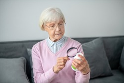 Healthcare. Senior woman with magnifier scrutinizing the medicines