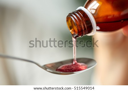 healthcare, treatment and medicine concept - bottle of medication or antipyretic syrup and spoon - Shutterstock ID 515549014