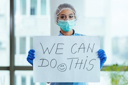 Healthcare worker holding placard with supportive 'we can do this' message while standing in the hospital.