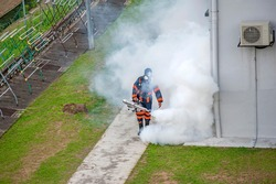 Healthcare worker using Fogging machine spraying chemical to eliminate mosquitoes and kill larvae to fight against the spread of dengue fever, Zika virus or Malaria at a residential area.