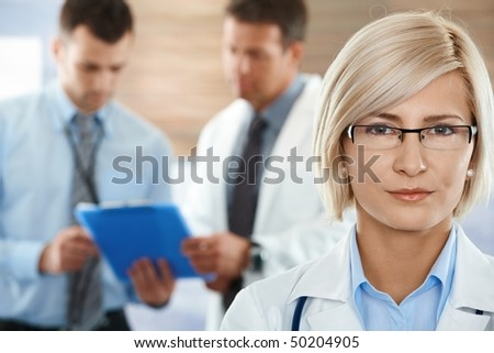 Healthcare workers on hospital corridor female doctor in front looking at camera.