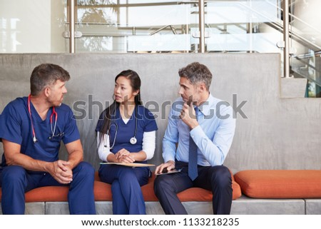 Healthcare workers talk sitting on a bench in hospital