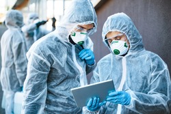 Healthcare workers wearing hazmat suits working together to control an outbreak