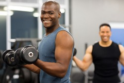 healthy african man working out with dumbbells in gym