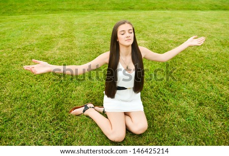 Healthy and happy woman meditating in the park