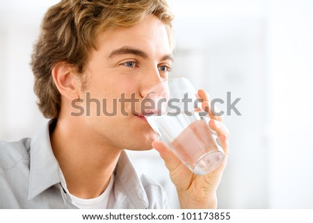 Healthy and happy young man drinking water while relaxing at home