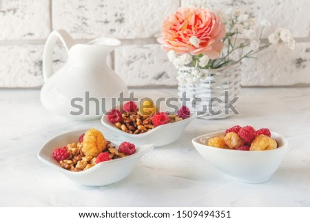 Healthy and healthy Breakfast of muesli and fresh raspberries and strawberries with yogurt on a light background. Copy space