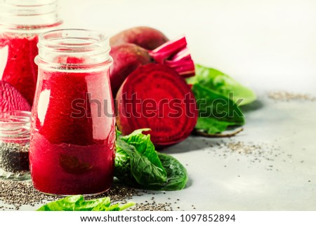 Healthy and healthy detox smoothies or juice from raw beets and spinach with chia seeds in glass bottles on a gray background, selective focus