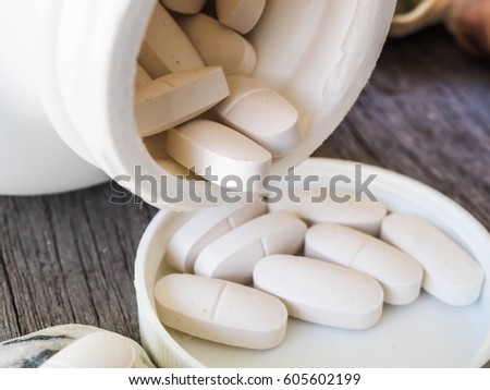 Healthy and Nature Concept: Calcium white tablet a good supplement for woman bone,In a white bottle incline,
