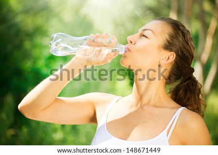 Healthy and Sporty Young Woman Drinking Water from the bottle. Doing Sport Outdoor.