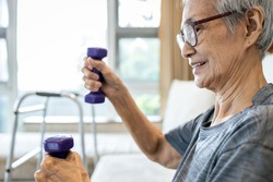 Healthy and strong in old age,Happy smiling asian senior woman working out with heavy dumbbells,lifting dumbbell weight for strength training,elderly grandmother exercise regularly,health care concept