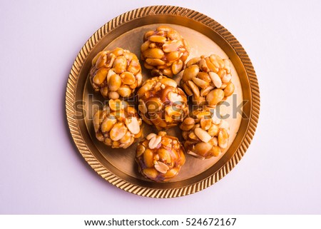 Healthy and sweet groundnut or peanut and Jaggery Laddoo, served in a brass plate isolated over white background. selective focus