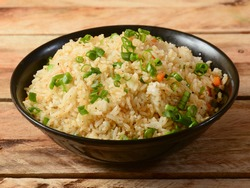 Healthy and tasty veg fried rice made of mixed veggies served in bowl over a rustic wooden background, Indo chinese, Indian cuisine, selective focus