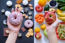 Healthy and unhealthy food concept, apple and donut in hand. Top view