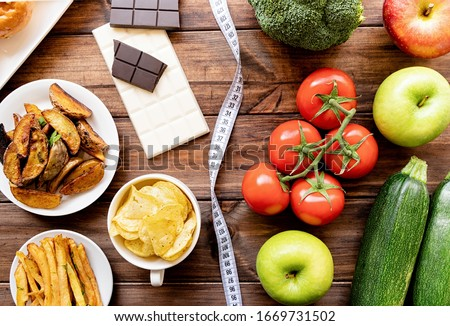 Healthy and unhealthy food concept. Fruit and vegetables vs sweet and potatoe fries top view flat lay on rustic background Stock photo ©