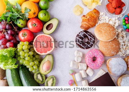 Healthy and unhealthy food concept. Top view of fast and sweet food vs fruit and vegetables