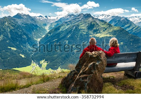 healthy and vital senior couple sitting on bench in austrian alps with beautiful view
