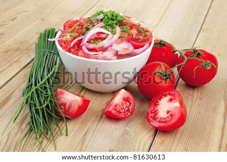 healthy appetizer : fresh tomato salad in white bowl with bunch of chives and raw tomatoes on twig , violet onion, over wooden table