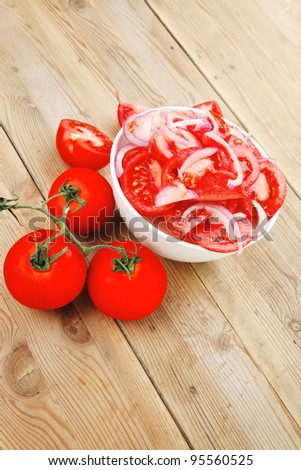 healthy appetizer : fresh tomato salad with onion in white bowl over wood