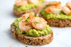 Healthy appetizer or snack avocado shrimp bruschetta with whole grain bread on white marble, closeup view. Fried shrimp and mashed avocado on a toasted bread